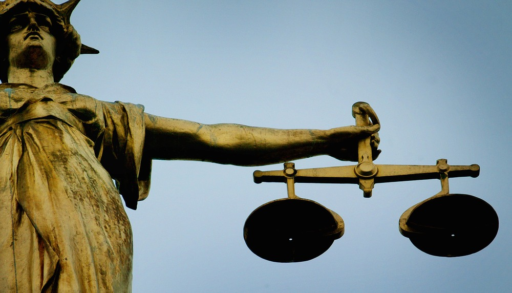 A statue holding the scales of justice is seen on top of the Old Bailey in London, December 12, 2003. REUTERS/Stephen Hird SH/ASA/AA - RP4DRIFSXQAA