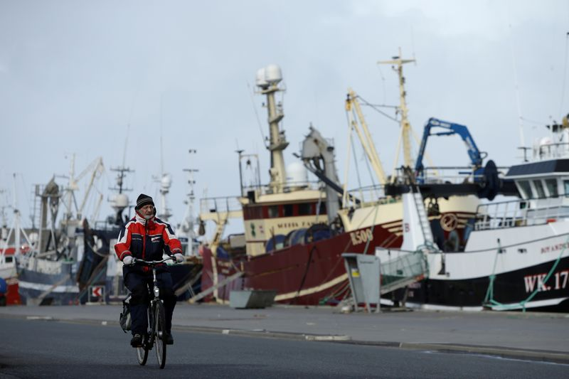 FILE PHOTO: A man rides his bicycle past a row of docked fishing ships in the village of Thyboron in Jutland, Denmark, March 17, 2019. REUTERS/Andrew Kelly