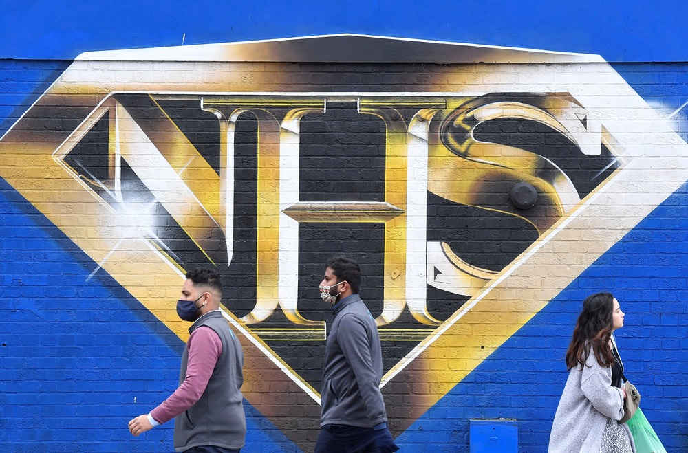 FILE PHOTO: People walk past a mural praising the NHS (National Health Service) amidst the continuation of the coronavirus disease (COVID-19) pandemic, London, Britain, March 5, 2021. REUTERS/Toby Melville