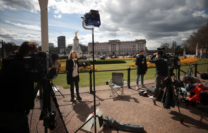 Members of the media report outside Buckingham Palace after it was announced that Britain's Prince Philip, husband of Queen Elizabeth, has died at the age of 99, in London, Britain, April 9, 2021. REUTERS/Hannah McKay