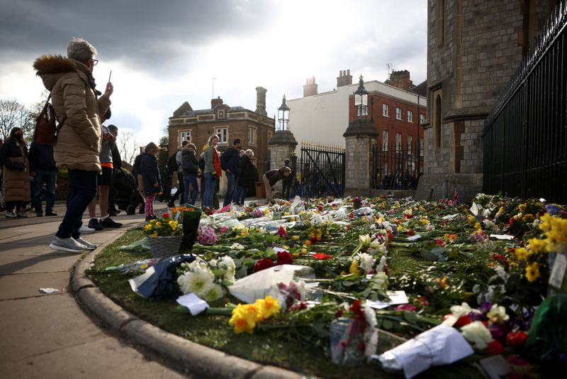 People observe flowers outside Windsor castle, after Britain's Prince Philip, husband of Queen Elizabeth, died at the age of 99, in Windsor, near London, Britain, April 11, 2021. REUTERS/Henry Nicholls