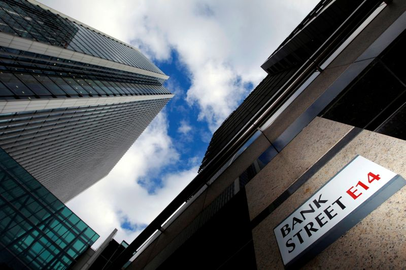 A sign for Bank Street and high rise offices are seen in the financial district in Canary Wharf in London, Britain, October 21, 2010. REUTERS/Luke Macgregor//File Photo