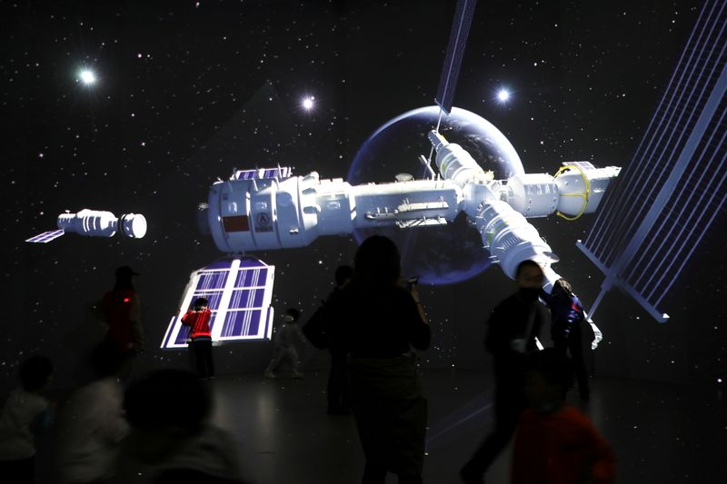 Visitors stand near a giant screen displaying the images of the Tianhe space station at an exhibition featuring the development of China's space exploration on the country's Space Day at China Science and Technology Museum in Beijing, China April 24, 2021. REUTERS/Tingshu Wang