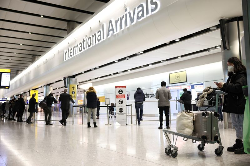 Travellers stand at Terminal 2 of Heathrow Airport, amid the coronavirus disease (COVID-19) outbreak in London, Britain February 14, 2021. REUTERS/Henry Nicholls/File Photo