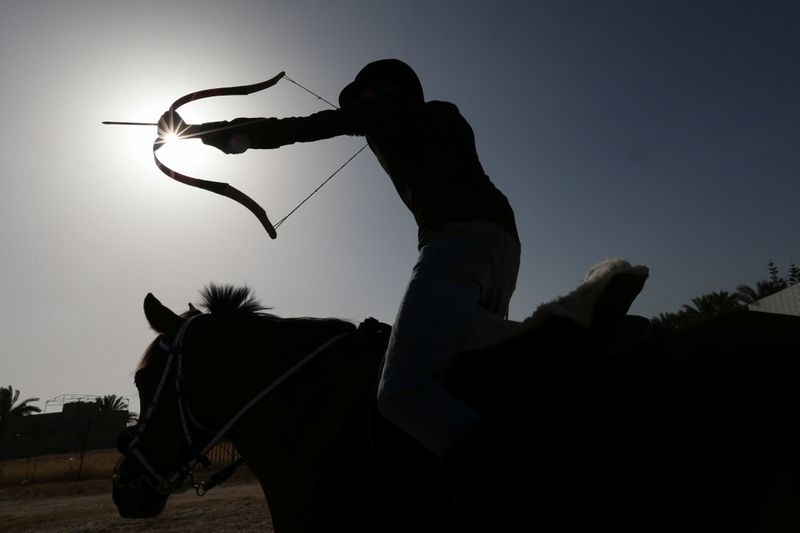 A young Palestinian rider shoots an arrow at a target during a horseback archery training session in Zawayda in the central Gaza Strip April 28, 2021. Picture taken April 28, 2021. REUTERS/Ibraheem Abu Mustafa