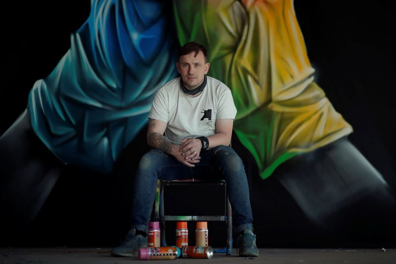 FILE PHOTO: Street artist Nathan Murdoch poses for a picture in front of his artwork after he creates a piece of crypto art to be auctioned with proceeds donated to the NHS in Peterborough, Britain, April 15, 2021. REUTERS/Andrew Couldridge