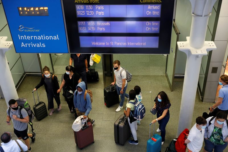 Passengers wearing protective face masks arrive from Paris at Eurostar terminal at St Pancras station, as Britain imposes a 14-day quarantine on arrival from France from Saturday, following the outbreak of the coronavirus disease (COVID-19), in London, Britain August 14, 2020. REUTERS/Peter Nicholls