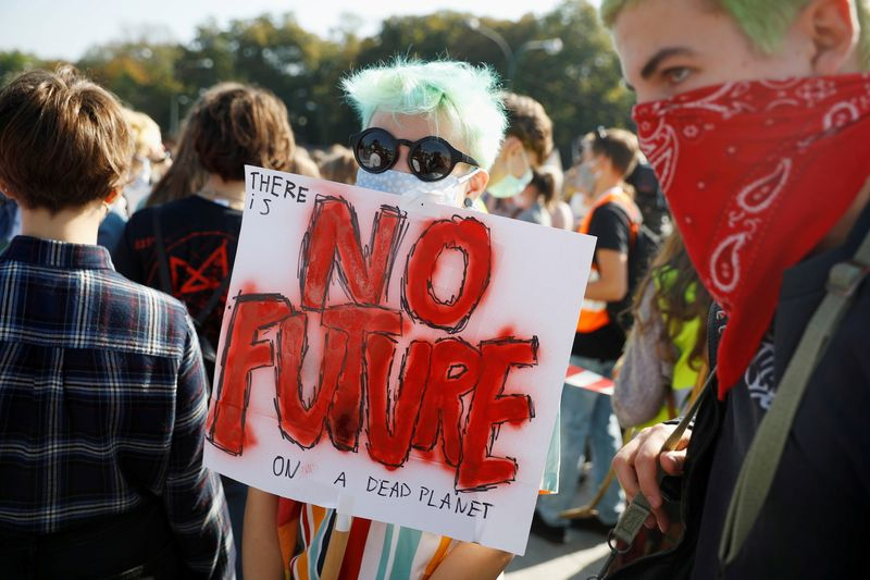 """FILE PHOTO: A person holds a sign as Fridays for Future protesterss demonstrate for a """"Global Day of Climate Action"""" in Warsaw, Poland, September 25, 2020. REUTERS/Kacper Pempel/File Photo"""