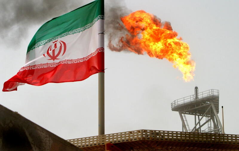 FILE PHOTO: A gas flare on an oil production platform is seen alongside an Iranian flag in the Gulf July 25, 2005. REUTERS/Raheb Homavandi/File Photo