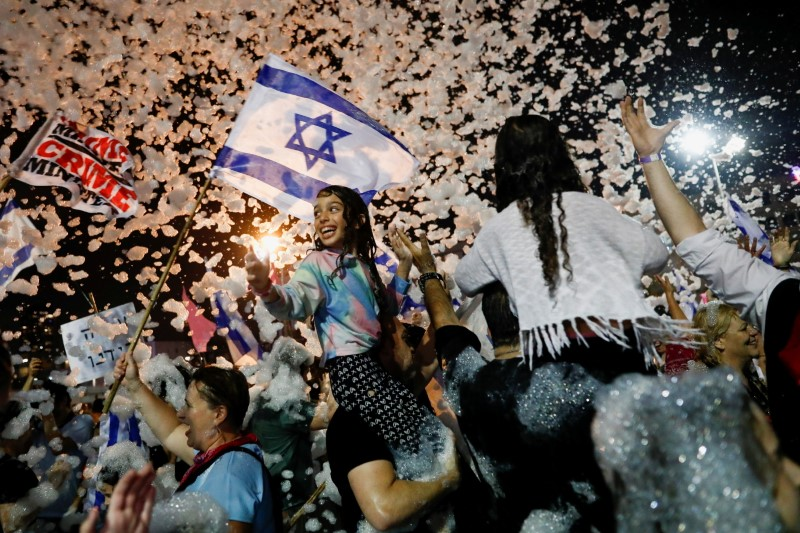 FILE PHOTO: People celebrate after Israel's parliament voted in a new coalition government, ending Benjamin Netanyahu's 12-year hold on power, at Rabin Square in Tel Aviv, Israel June 13, 2021. REUTERS/Corinna Kern