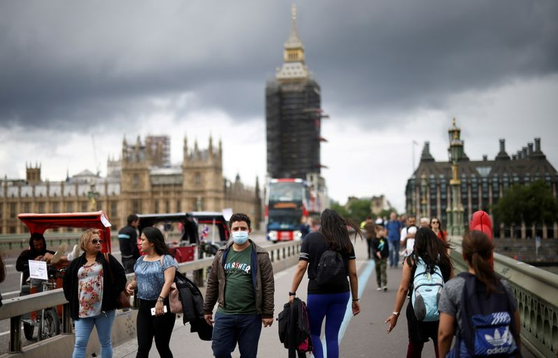 FILE PHOTO: People, some wearing protective face masks, walk over Westminster Bridge, amid the coronavirus disease (COVID-19) pandemic, in London, Britain, July 4, 2021. REUTERS/Henry Nicholls/File Photo