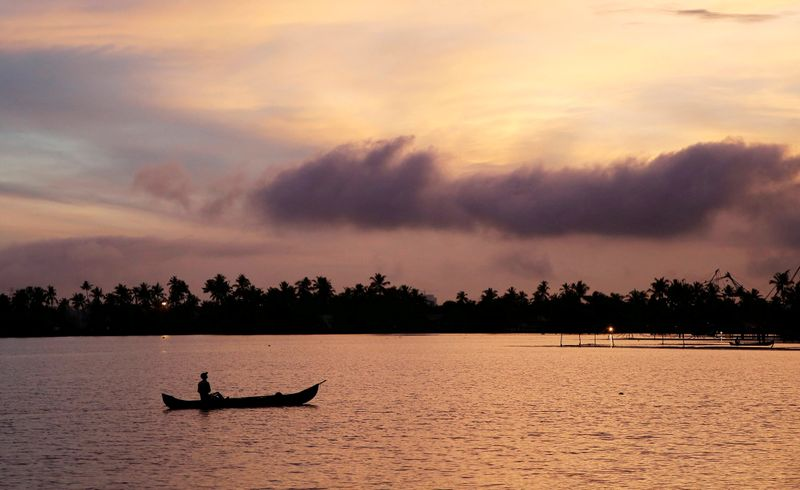 FILE PHOTO: A man rows his boat in the tributary waters of Vembanad Lake against the backdrop of pre-monsoon clouds on the outskirts of Kochi, India, June 7, 2019. REUTERS/Sivaram V/File Photo