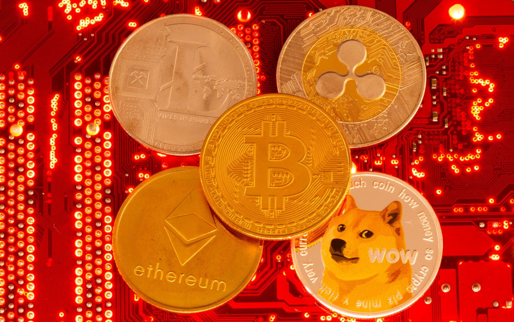 Representations of cryptocurrencies Bitcoin, Ethereum, DogeCoin, Ripple, Litecoin are placed on PC motherboard in this illustration taken June 29, 2021. REUTERS/Dado Ruvic/Illustration/File Photo