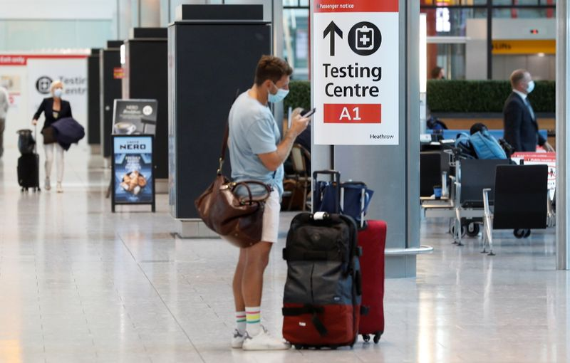 A passenger stands next to a COVID-19 testing centre sign in the International arrivals area of Terminal 5 in London's Heathrow Airport, Britain, August 2, 2021. REUTERS/Peter Nicholls