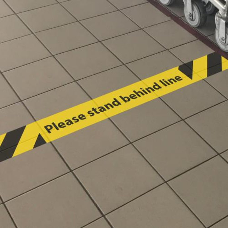 Please stand behind line social distancing graphics installation