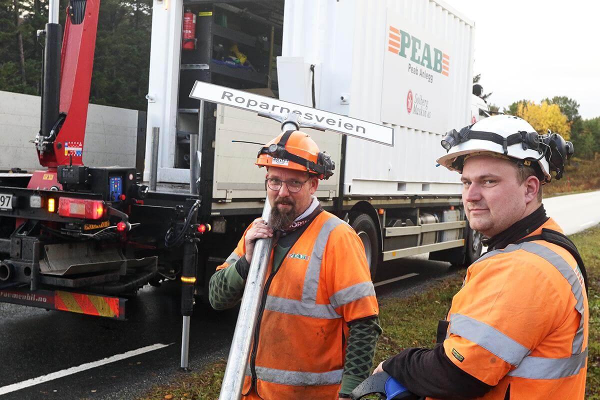 Rune Møllslet (til venstre) og Odd Arne Renå har fått jobben med å montere veinavnskilt for fylkeskommunen, og onsdag fikk Roparnesveien sitt skilt på Langstranda på Glasøya.