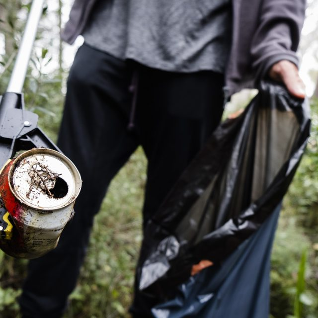 man collecting garbage in the forest