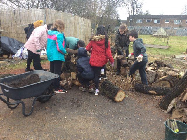 kids lifting chunks of wood