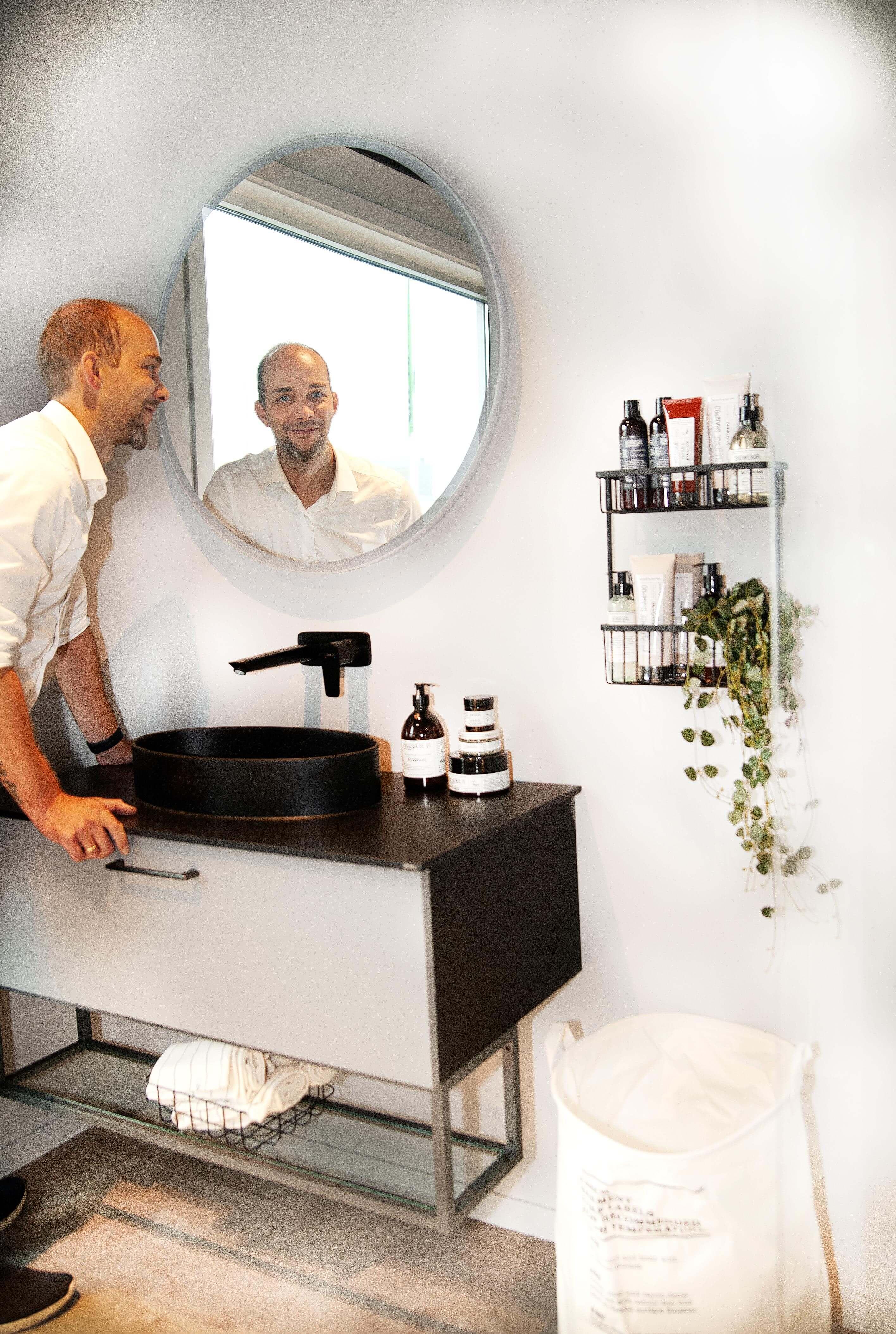 Butikkmedarbeider Marius Klæbo ved ei av baderomsinnredningene du kan se. HTH Kjøkkenforum leverer også løsninger til vaskerom og skyvedørsgarderober.