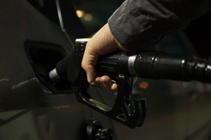 Close of hand using fuel pump of person looking at how to sell a car