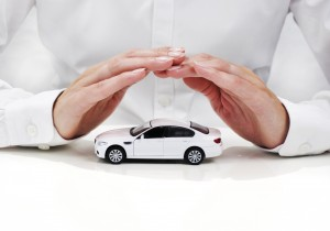Hands shielding a car to signify car insurance