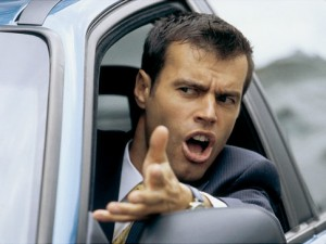 An angry driver shouting and gesturing out of the window of his car