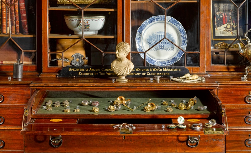 A close up of a cabinet with an open drawer covered in watches and various items stored in the glazed bookcase