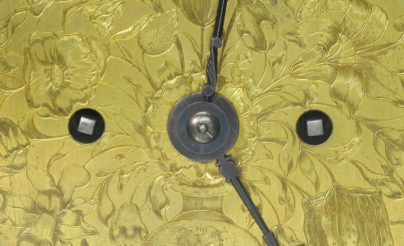a close up of a clock dial showing the winding holes, clock hands and engraving