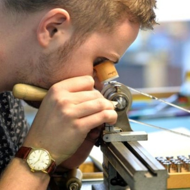 person at watchmakers lathe