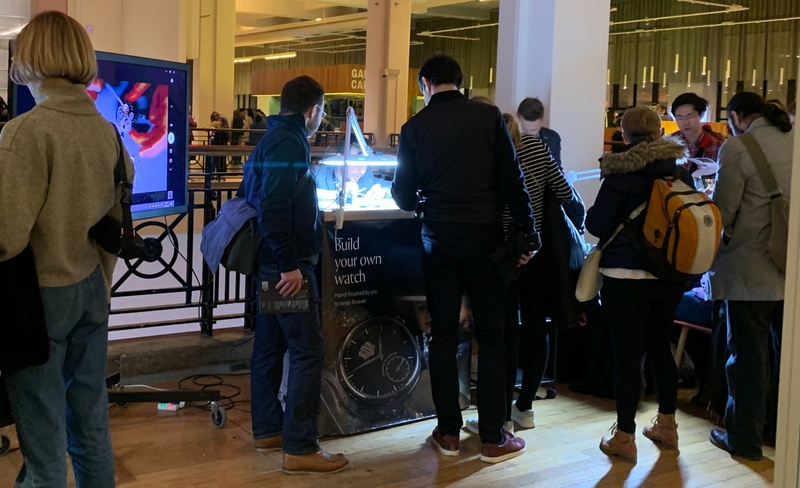 People grouped around a lit bench where a watchmaker works