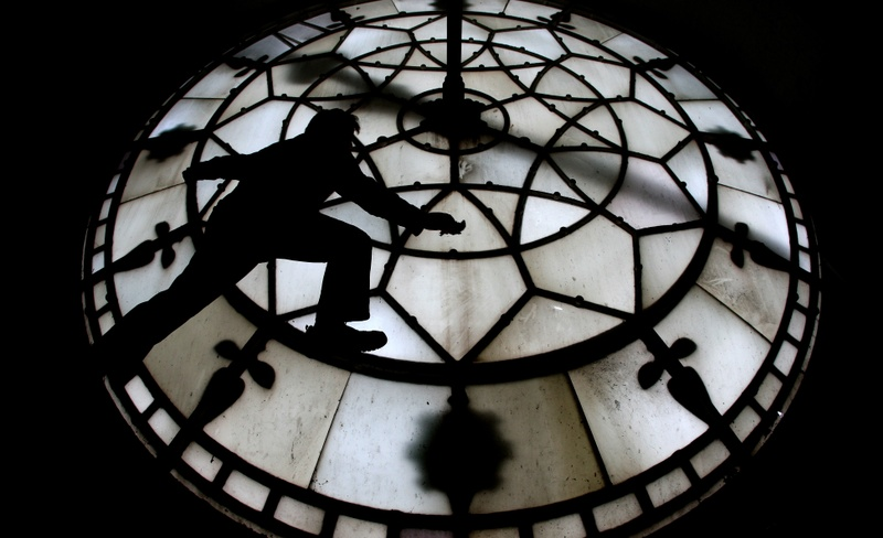 A man stepping on the frame of a glass dial to clean it