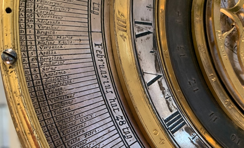 a close up of the clock dial showing the saint's names for each day