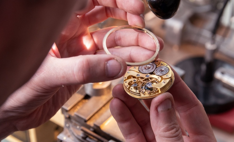 A watchmaker offering up a part for fitting to the watch