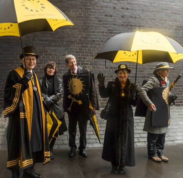 Men and women holding black and gold umbrellas and dressed in black and gold robes