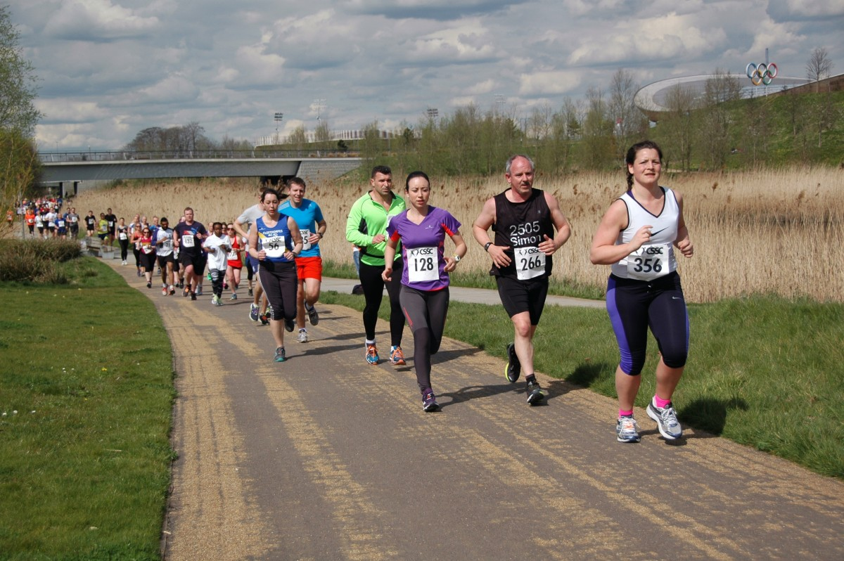 A large, mixed group of adults run along a country road during a race