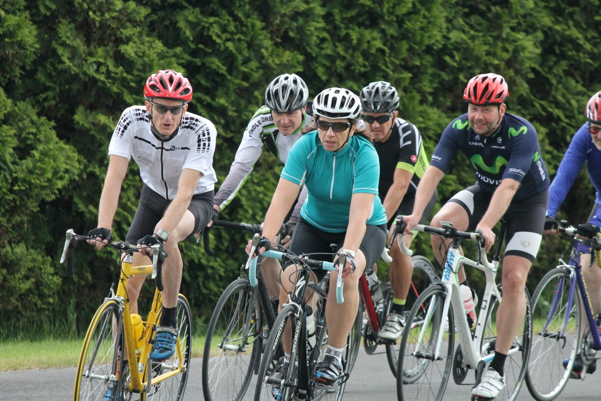 A group five cyclists in full cycling gear race on roadbikes