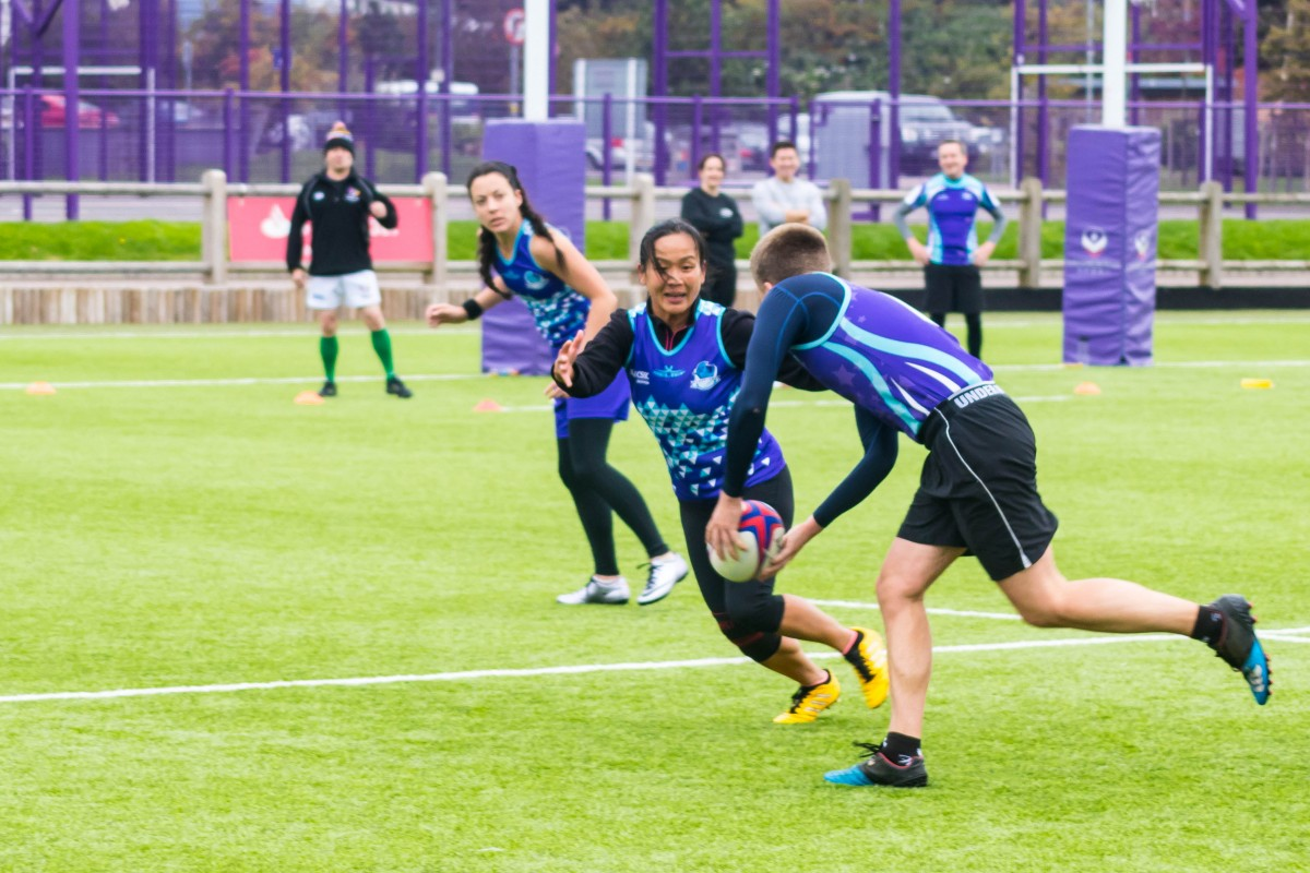 A group of young people wearing blue team shirts play touch rugby outdoors