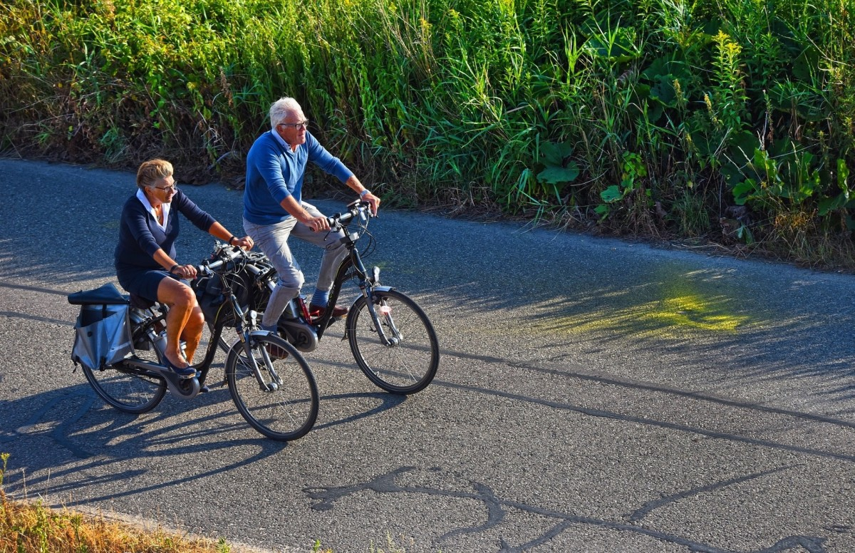 An older couple ride side by side on city bikes