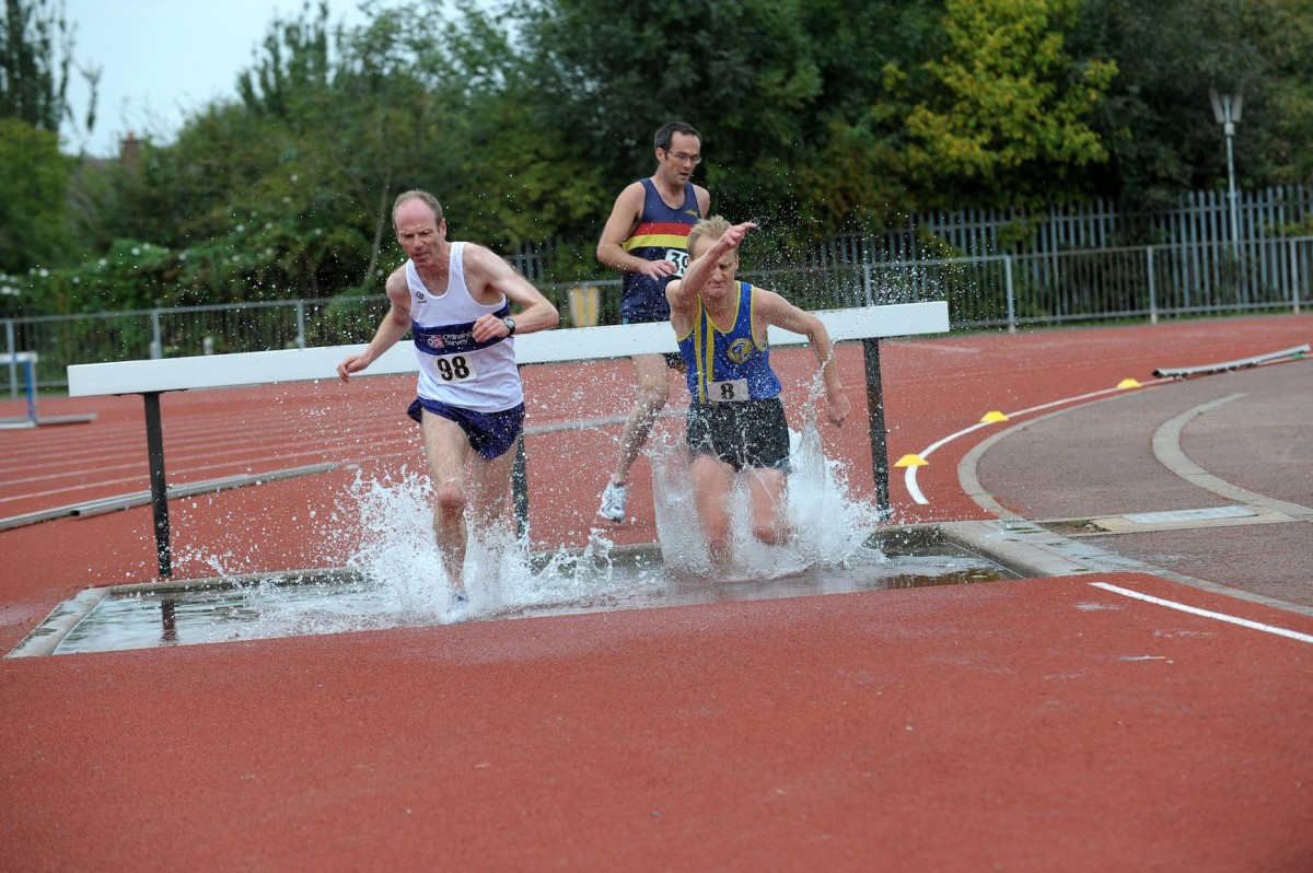 Three runners clear a hurdle on an athletics track, with a water trough behind the hurdle