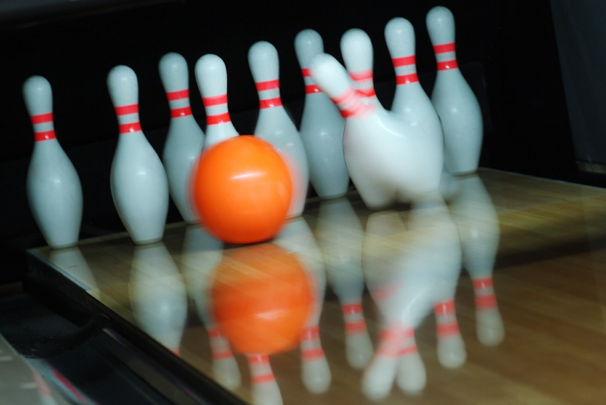 An orange bowling ball makes contact with the triangle of pins, knocking the first pin over