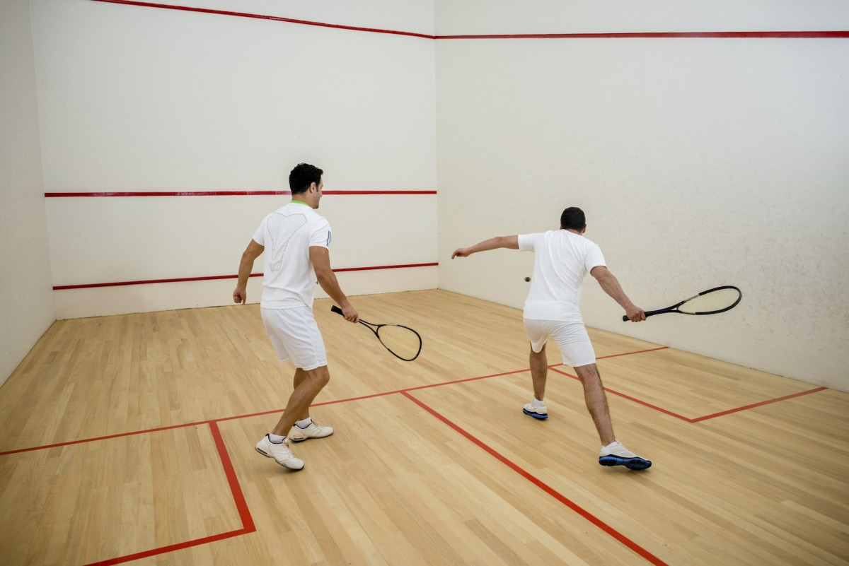 Two men wearing white play squash together in a red and white court
