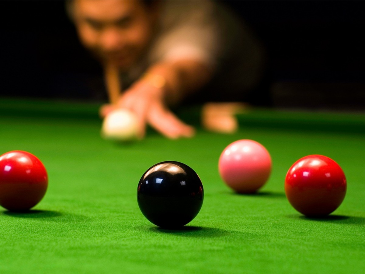 A snooker player lines up a shot on the black, the balls are in the foreground of the picture and the snooker player is in the background, out of focus
