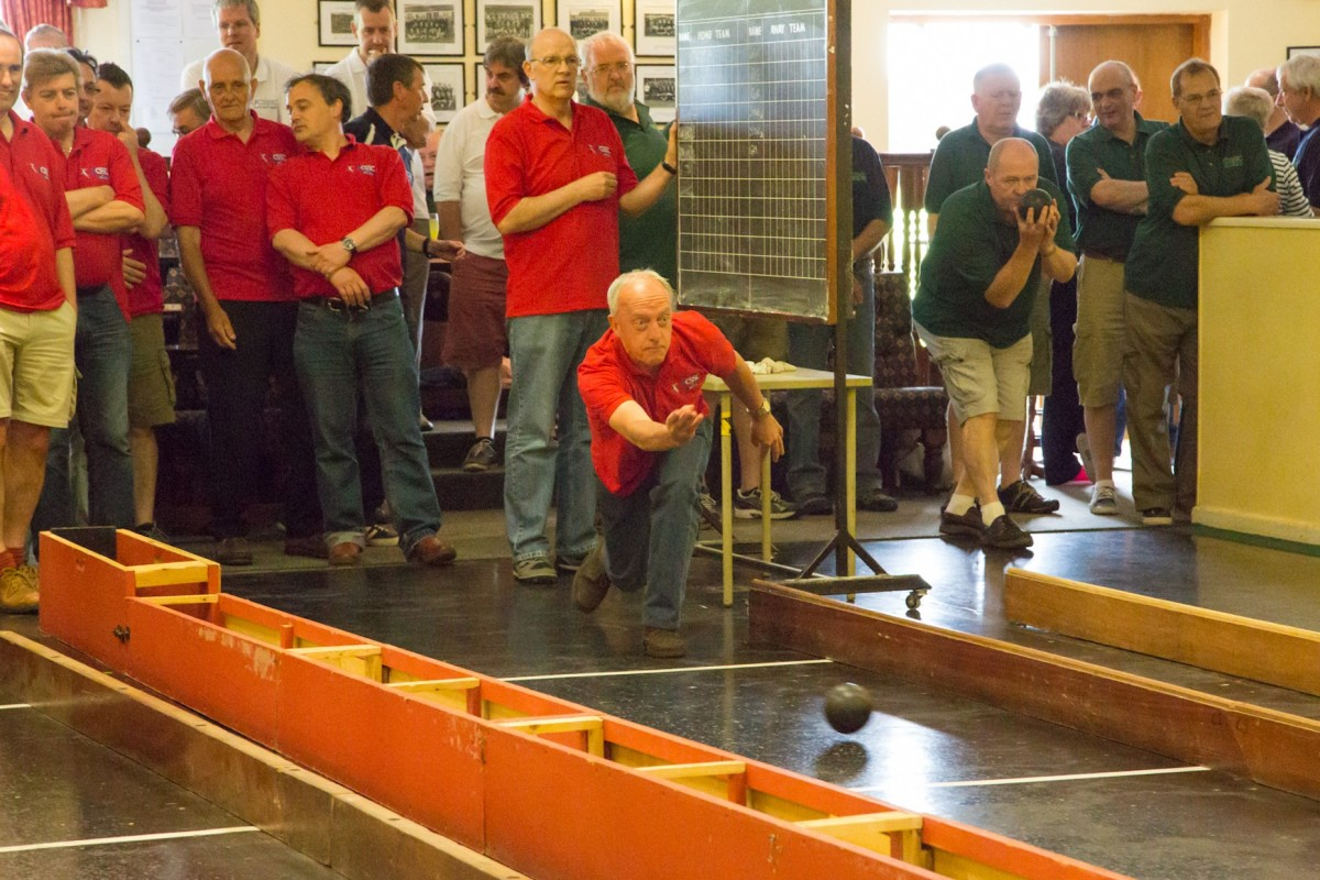 A mixed group of adults, a red team vs a blue team, play skittles indoors