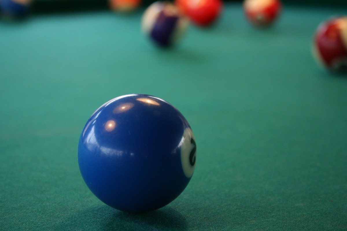 A close up of a blue spot ball on the green felt of a pool table