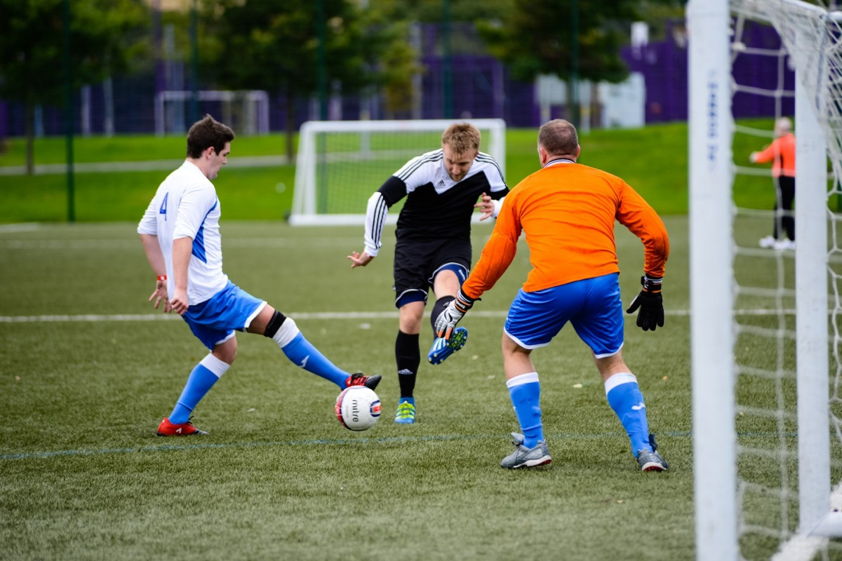 A player goes to tackle another player on an outdoor, grass football pitch