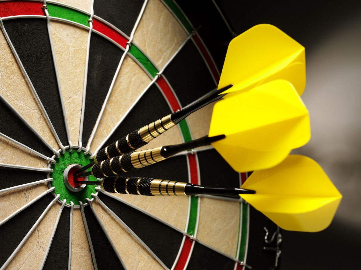 A close up of three darts with yellow flyers in the bullseye of the dart board