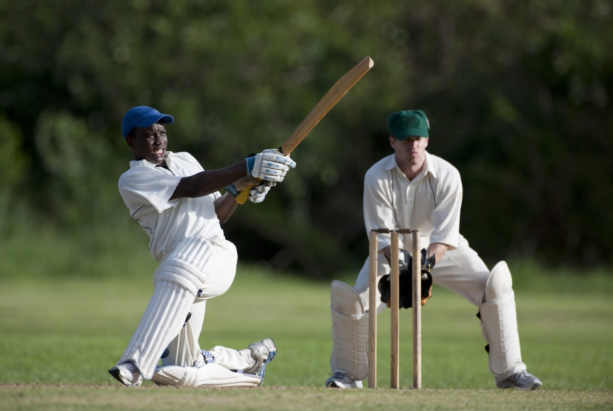 A batsman kneels down with the bat extended at the end of a swing. The wicketkeeper is bend down ready