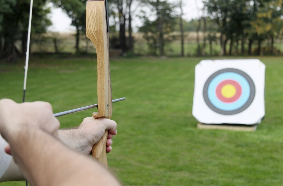 A close up of a bow being drawn back, aimed at a target in a field