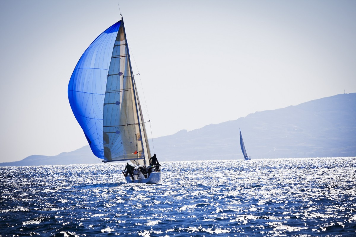 A sailboat with a large blue sail on the water with a mountain on the horizon