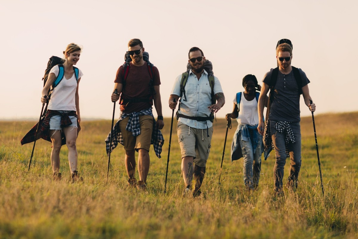 A group of five walkers in walking gear walk down a hill together whilst the sun is setting